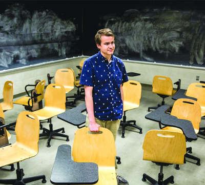 student standing in an empty classroom